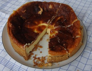 The cheesecake on the plate being cut into pieces for hungry colleagues.