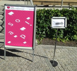Pink poster of the soap! conference with another small sign showing arrow pointing to the right
