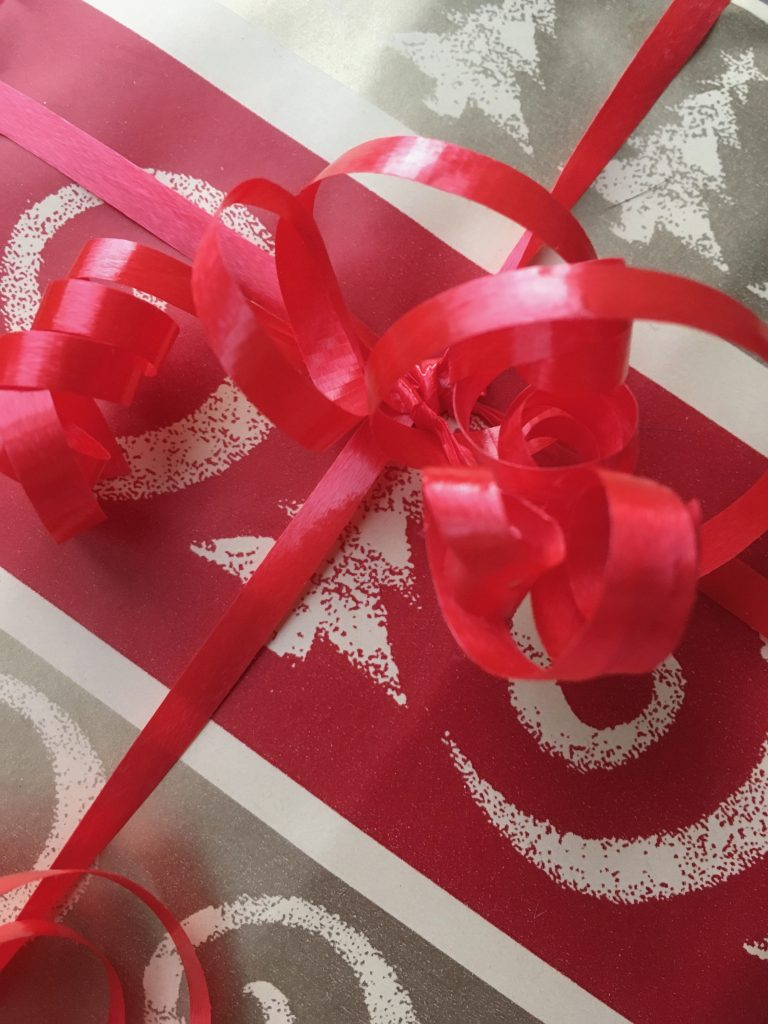 Close-up of red and gold striped wrapping paper tied with thin, curled, red ribbon